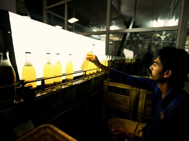A worker at Pakistan's lone beer maker, Murree Brewery, checks the quality of bottles at the factory in Rawalpindi November 10, 2012. PHOTO: REUTERS