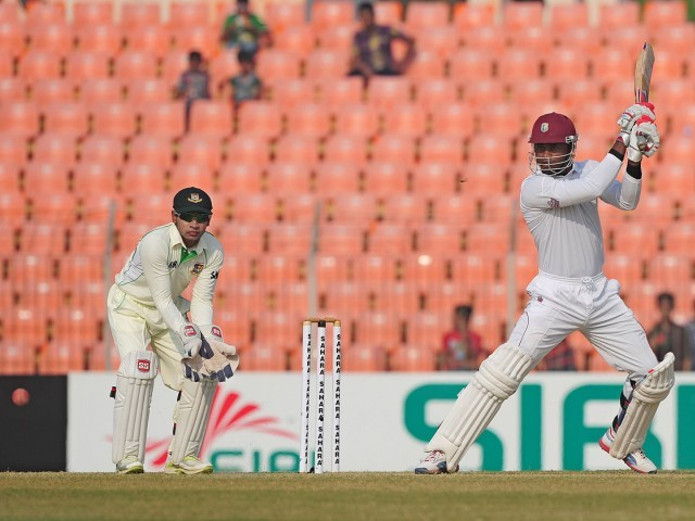 West Indies batsman Marlon Samuels (R) plays a shot as Bangladesh cricket captain Mushfiqur Rahim (L) looks on. PHOTO: AFP