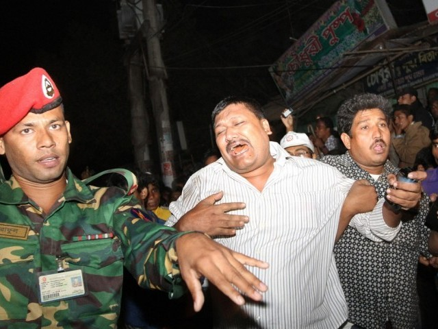 This picture taken on November 24, 2012 shows a man (C) mourning as he is supported by a man (R) after his relative was killed under the debris of three girders of an under-construction flyover in Chittagong.  PHOTO: AFP