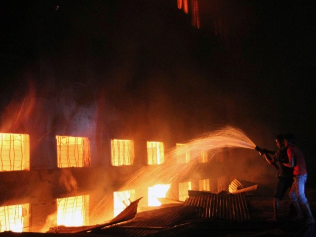 This picture taken on 24 November, 2012 shows Bangladeshi people and firefighters trying to extinguish a fire in a garment factory in Savar, 30 kilometres north of Dhaka. PHOTO: AFP