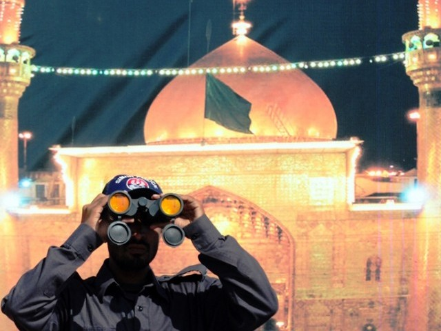 A Pakistani policeman looks through binoculars during a Shiite Muslim religious procession in Karachi on November 23, 2012. PHOTO: AFP