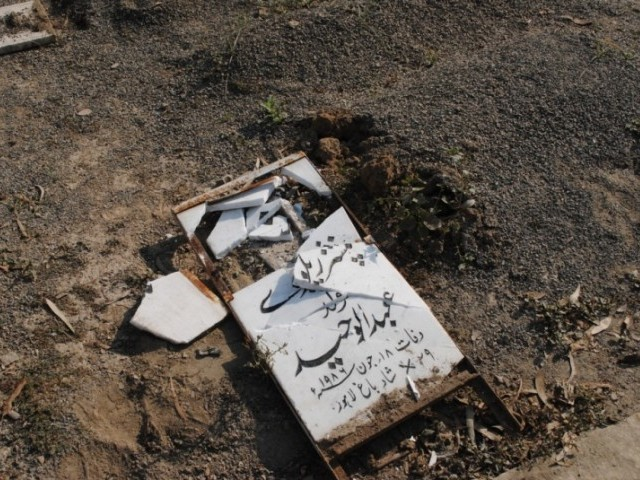 A tombstone desecrated by unidentified men at the graveyard. PHOTO: RABIA MEHMOOD