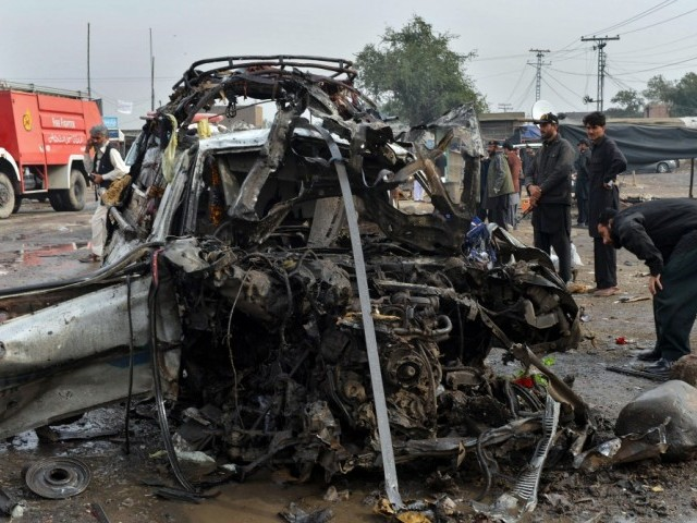 Pakistani security officials examine the wreckage of a destroyed vehicle at the site of a car bomb attack in Jamrud in Khyber district on December 17, 2012.  PHOTO: AFP