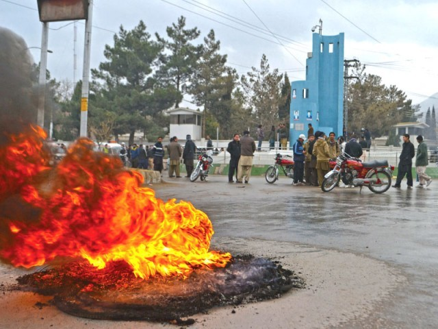 Protesters gather near burning tyres as they demonstrate against the killing of Khadim Hussain Noori, Director of Public Relations in Quetta. PHOTO: AFP