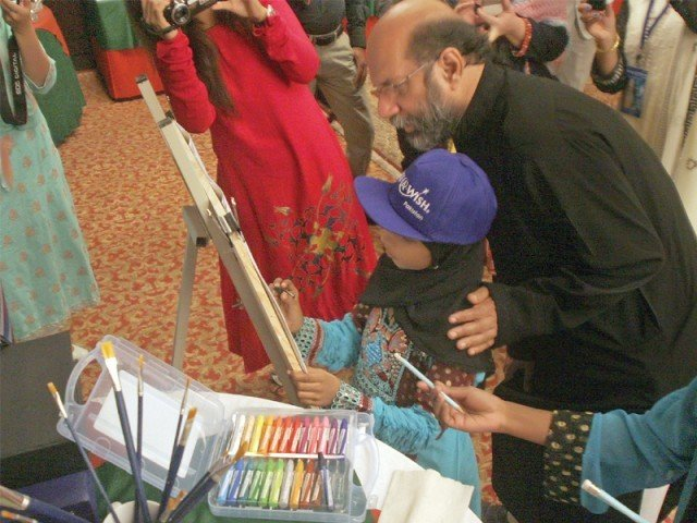 Rimsha Khan, suffering from a tumour in one of her legs that has spread to her abdomen, paints with help from artist Jimmy Engineer at the event organised at Sheraton hotel. PHOTO: ATHAR KHAN/ EXPRESS