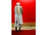 An old man gets ready to offer namaz against the red backdrop of the shrine. PHOTO: FASEEH SHAMS