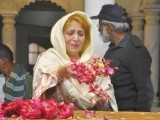 A Pakistan People's Party (PPP) member scatters rose petals on the grave of assassinated former prime minister Benazir Bhutto, marking her death anniversary, at the Bhutto family mausoleum in Garhi Khuda Bakhsh, near Larkana December 26, 2012. PHOTO : REUTERS
