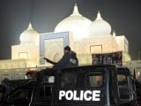 A Pakistani policeman stands guard outside the tomb of former Prime Minister Benazir Bhutto in Garhi Khuda Bukash near Larkana on December 26, 2012, to commemorate the fifth anniversary of her death.  PHOTO : AFP
