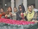 Pakistan Peoples Party (PPP) supporters scatter rose petals on the grave of Pakistan's former Prime Minister Benazir Bhutto during her death anniversary at the Bhutto family mausoleum in Garhi Khuda Bakhsh, near Larkana December December 27, 2012. PHOTO : REUTERS