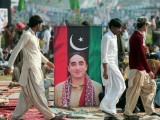 Pakistani supporters walk past the portrait of Bilawal Bhutto Zardari, chairman of ruling Pakistan People's Party (PPP) outside the Bhutto family mausoleum in Garhi Dera Bakhsh on December 27, 2012, on the fifth anniversary of the assassination of Benazir Bhutto. PHOTO : AFP