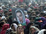 A Pakistani supporter carries a portrait of former Pakistan premier Benazir Bhutto outside the Bhutto family mausoleum in Garhi Dera Bakhsh on December 27, 2012, on the fifth anniversary of the assassination of Benazir Bhutto. PHOTO : AFP