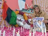 A supporter of the ruling Pakistan Peoples Party (PPP) lights candles at the site where former premier Benazir Bhutto was assassinated, on her fifth death anniversary in Rawalpindi on December 27, 2012. PHOTO : AFP