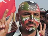 An activist of the ruling Pakistan People's Party (PPP) shows a victory sign with painted party flag on his face outside the Bhutto family mausoleum in Garhi Dera Bakhsh on December 27, 2012, on the fifth anniversary of the assassination of Benazir Bhutto. PHOTO : AFP