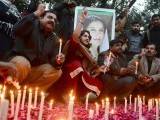 Activists of ruling Pakistan People's Party (PPP) shout slogans as they sit in front of a portrait of the late former Pakistan premier Benazir Bhutto during a candlelight ceremony in Lahore on December 27, 2012, on the fifth anniversary of her assassination.  PHOTO : AFP