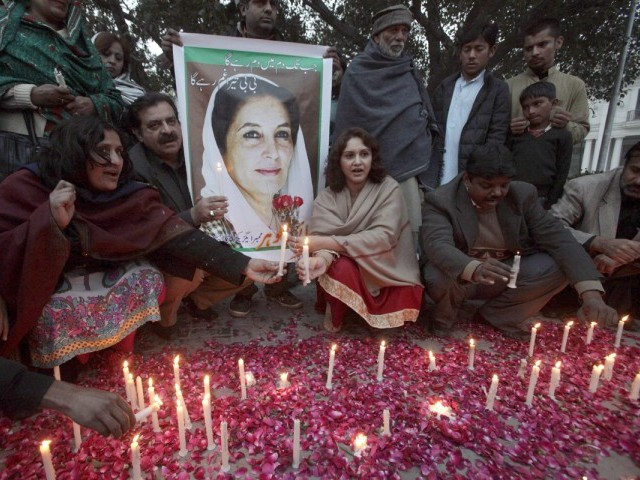 Pakistan Peoples Party (PPP) supporters light candles beside a poster of Pakistan's former Prime Minister Benazir Bhutto during her death anniversary in Lahore December 27, 2012. PHOTO : REUTERS