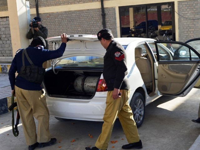 Policemen inspect a car after unknown armed men shot dead two men at a market in it in Charsadda on January 5, 2012. PHOTO: AFP