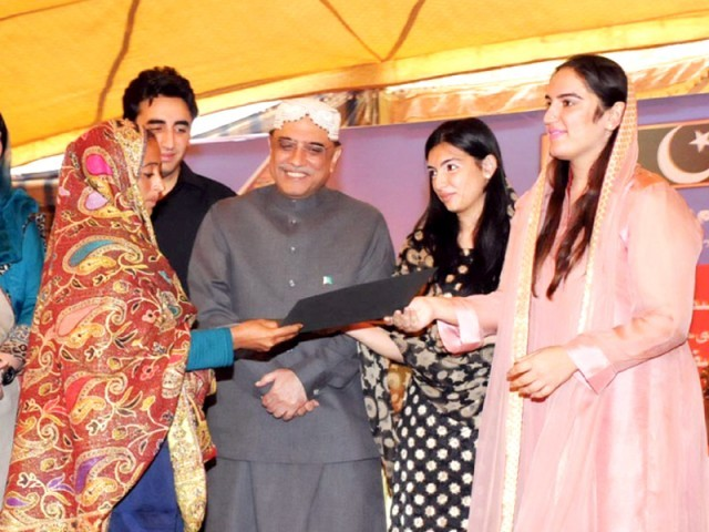 Bakhtawar Bhutto Zardari and Aseefa Bhutto Zardari hand over a certificate to a BISP beneficiary. PHOTO: ONLINE