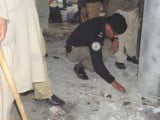 A policeman inspects the blast site inside the Tableeghi Markaz. PHOTO: FAZAL KHALIQ/EXPRESS