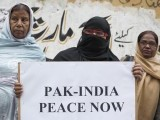 A member of Joint Action Committee (JAC), an alliance of civil society organizations, holds a placard while observing the global vigil for peace between India and Pakistan, in Karachi January 27, 2013. PHOTO : REUTERS