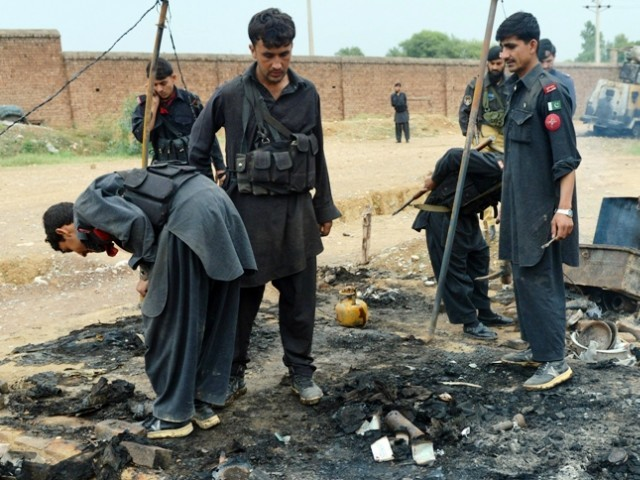 A file photo of security personnel inspecting a burnt out police checkpost following an attack by armed militants last year. PHOTO: AFP