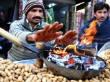 A vendor warms his hands to ward off cold during rain in Rawalpindi. PHOTO: ONLINE