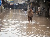A man walks through the standing water at Peepal Mandi, Peshawar. PHOTO: MUHAMMAD IQBAL/EXPRESS