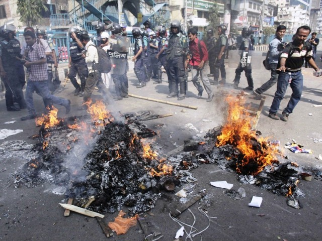 Police walk past piles of paper set alight by activists from 12 parties in front of the national mosque in Dhaka February 22, 2013. PHOTO: REUTERS