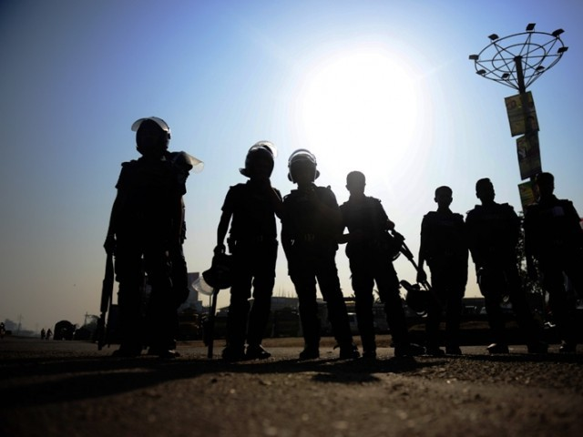 Bangladeshi police personnel stand guard during a nationwide strike in Dhaka on February 24, 2013. PHOTO: AFP
