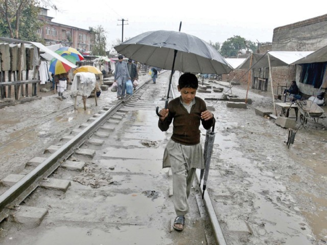 A child treading Hashtnagri Railway tracks. Peshawar received more than 15 millimetres of rain. PHOTO: PPI