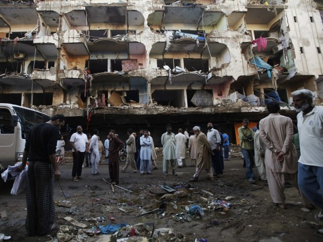 Residents gather in front of a damaged building after a bomb blast in a residential area, a day earlier, in Karachi March 4, 2013.  PHOTO: REUTERS