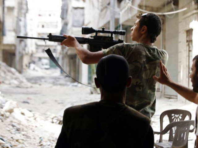 A Free Syrian Army fighter points his weapon during clashes with forces loyal to Syria's President Bashar al-Assad in Aleppo's al-Amereya district. PHOTO: REUTERS/ FILE