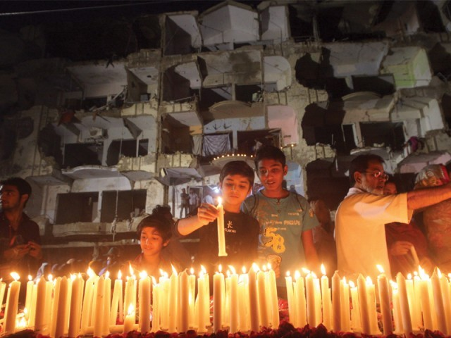 Friends, families and supporters light candles at the site of the blast on Friday in memory of the 50 people who lost their lives in the attack. PHOTO: ATHAR KHAN/EXPRESS
