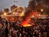 Revellers gather around a fire, alao, at the shrine. PHOTO: ABID NAWAZ/EXPRESS