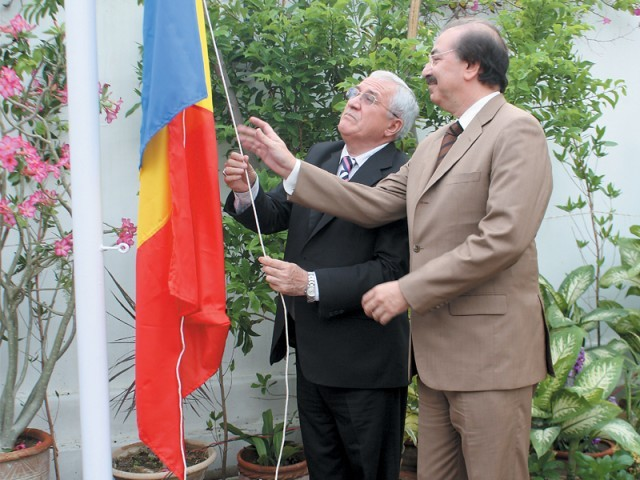 Romanian Ambassador Emilian Ion (left) and the new honorary consul of Romania, Tariq Saud (right), hoist the Romanian flag at the reopening of the consulate in Karachi on Monday. PHOTO: AMEER HAMZA/EXPRESS