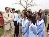 US ambassador Richard Olson shares a light moment with Pakistani students during a visit to a famous archeological site in Taxila. PHOTO: WAQAS NAEEM/FILE