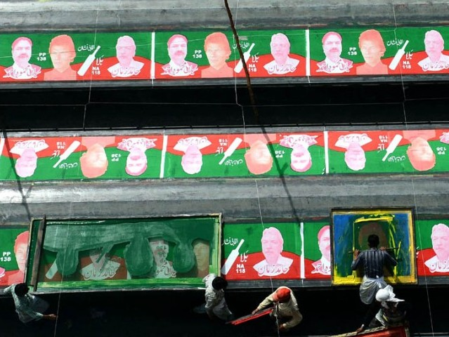 Workers prepare posters of the political party Pakistan Tehreek Insaf (PTI) in Lahore on April 13, 2013, for the upcoming general elections. PHOTO: AFP/FILE