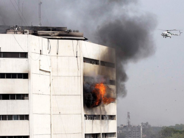 Flames and smoke spew out from the seventh floor of the building. PHOTO: SHAFIQ MALIK, ABID NAWAZ/EXPRESS