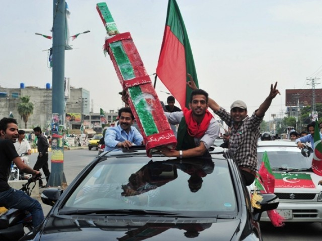 Activists of Pakistan Tehreek-e-Insaf (PTI) wave flags as they drive through the streets during the general election on May 11, 2013. PHOTO: AFP