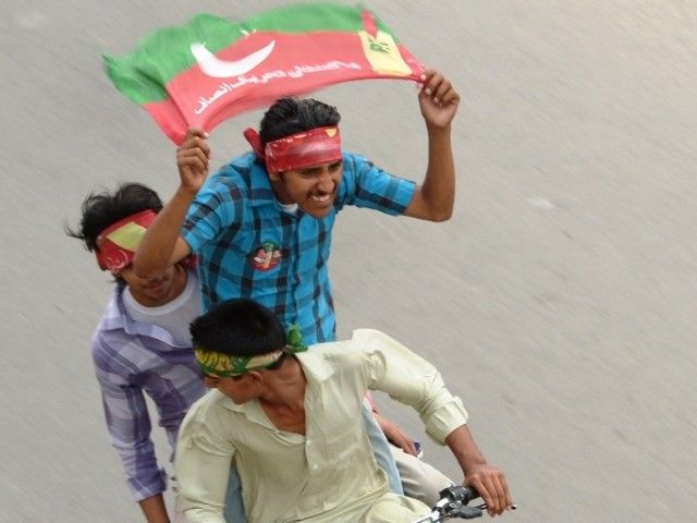 Activists of Pakistan Tehreek-e-Insaf (PTI) wave party flags as they drive through the streets during the general election in Rawalpindi on May 11, 2013. PHOTO: AFP