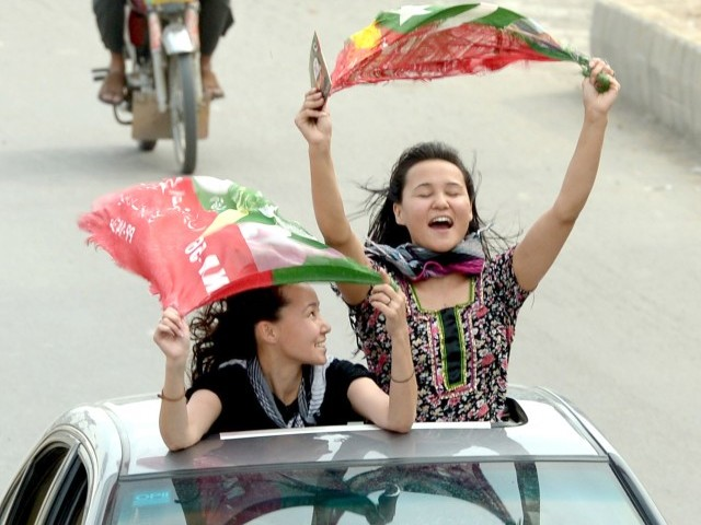 Activists of Pakistan Tehreek-e-Insaf (PTI) wave party flags as they drive through the streets during the general election in Rawalpindi on May 11, 2013. PHOTO : AFP