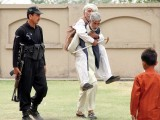 A person carrying an elderly person to the polling station to cast his vote. PHOTO: INP / ISLAMABAD