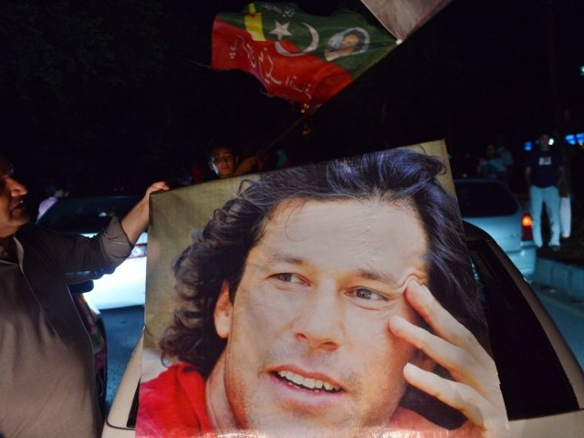 A PTI supporter carries Imran Khan's portrait as they take part in a rally in Islamabad on May 11, 2013. PHOTO: AFP