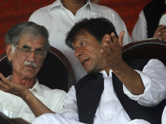 PTI chief Imran Khan talks with party leader Pervaiz Khattak. PHOTO: REUTERS/FILE