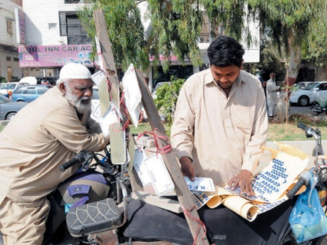 A person selling white license plates with the registration numbers in blue colour at Shahrah-e-Quaideen. Police has given 15 days to all motorcycle owners to change their fancy plates to standardised ones. PHOTO: RASHID AJMERI/EXPRESS