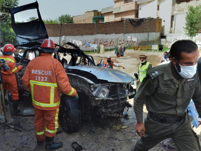 Volunteers search a badly damaged vehicle after a suicide bomb attack in Peshawar on May 24, 2013. PHOTO: AFP