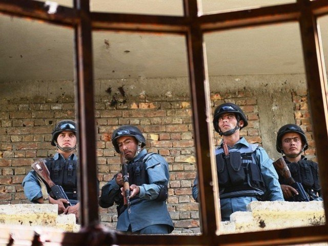 Afghanistan policemen stand guard in a building which was used for an attack.  PHOTO: AFP