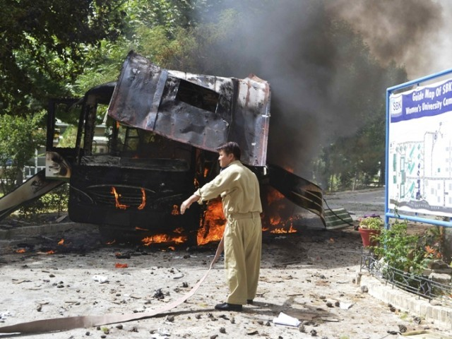 A firefighter stands near a burning bus after a bomb attack in Quetta June 15, 2013. PHOTO: REUTERS
