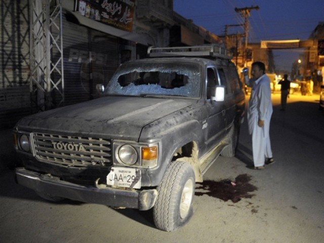 A Pakistani plainclothes police officer looks at a bullet-riddled vehicle after an attack by gunmen in Quetta on July 15, 2013. PHOTO: AFP