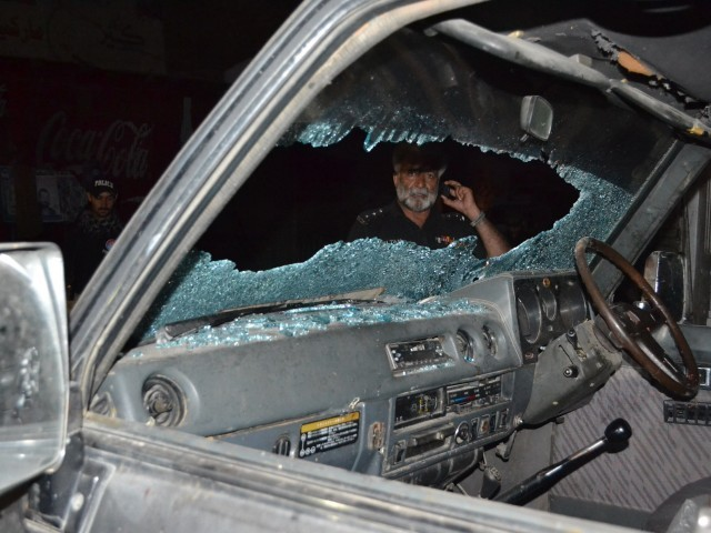 A Pakistani police officer looks at a bullet-riddled vehicle after an attack by gunmen in Quetta on July 15, 2013. PHOTO: AFP