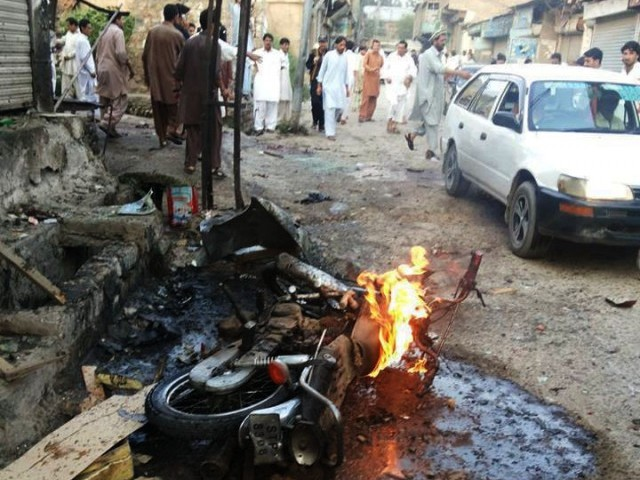 People gather around one of the blast sites in Parachinar on Friday. PHOTO: EXPRESS